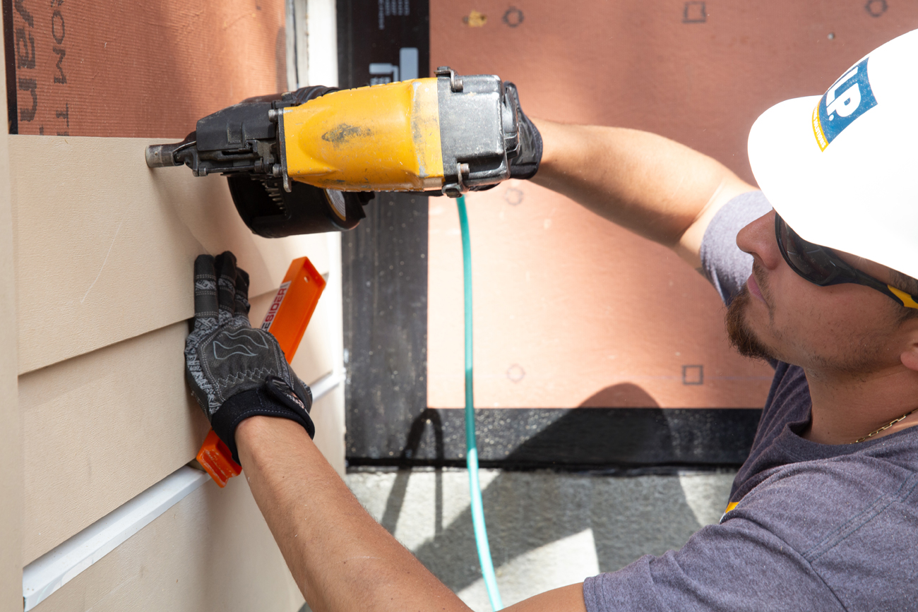 A worker in a hard-hat using power tools to apply horizontal siding to the outside of a wall.