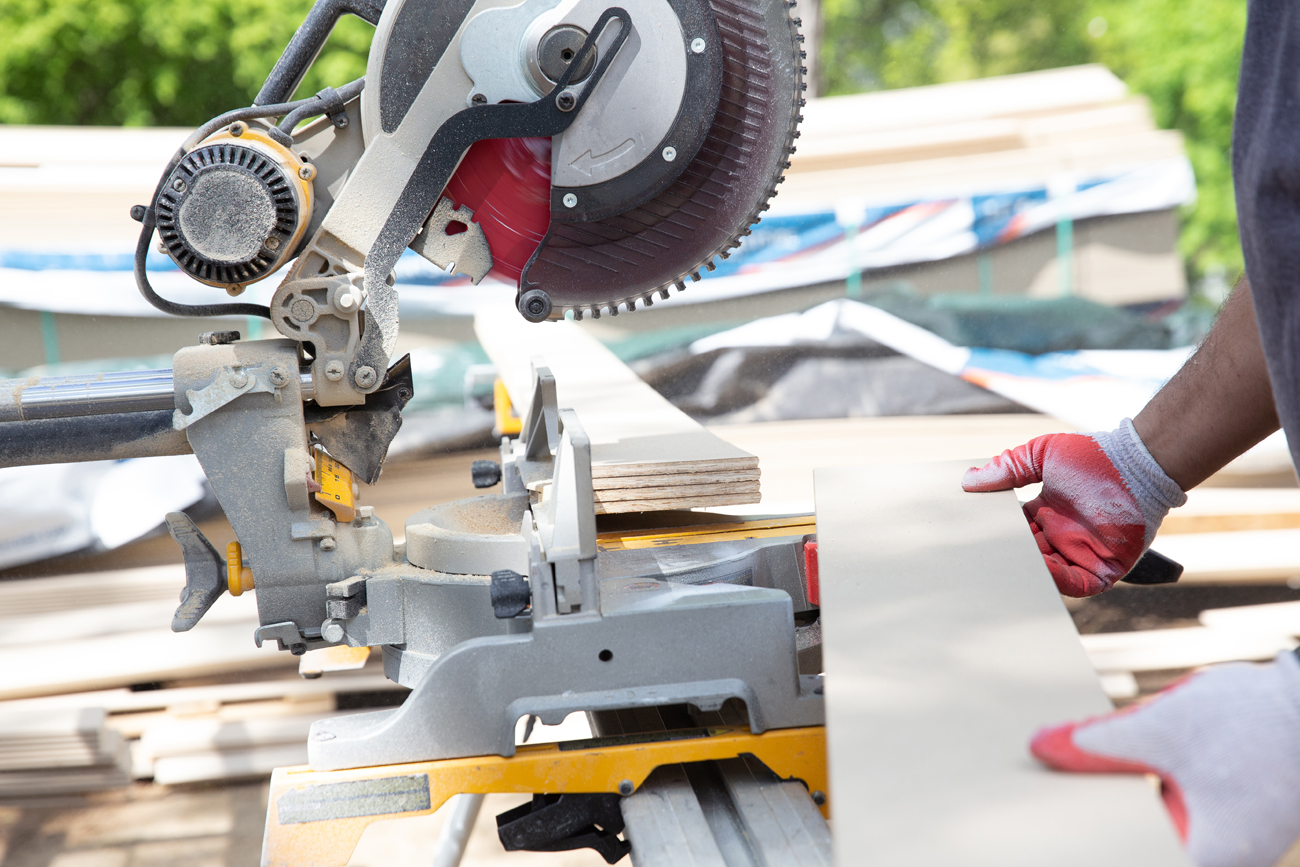 A worker in a hard-hat marking siding to be cut using a miter saw, outside in the sunshine.