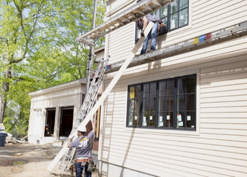A worker passing a siding panel up to another on a house construction site.