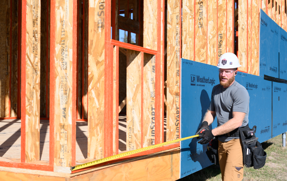 A worker measuring the outside edge of new construction framing to add a Weatherlogic panel