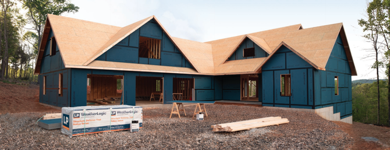 A new house under construction, fully covered in blue LP Weatherlogic panels