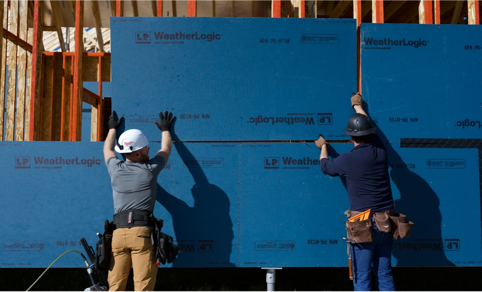 Two workers placing a sheet of LP WeatherLogic onto the outside of some construction framing.