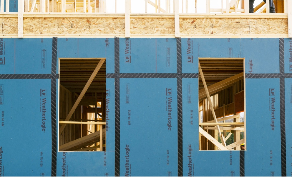 Blue Weatherlogic panels attched to the outside of a building under construction.
