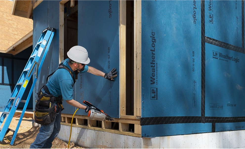 A worker attaching panels of Weatherlogic to the outside of a building using a nail gun.