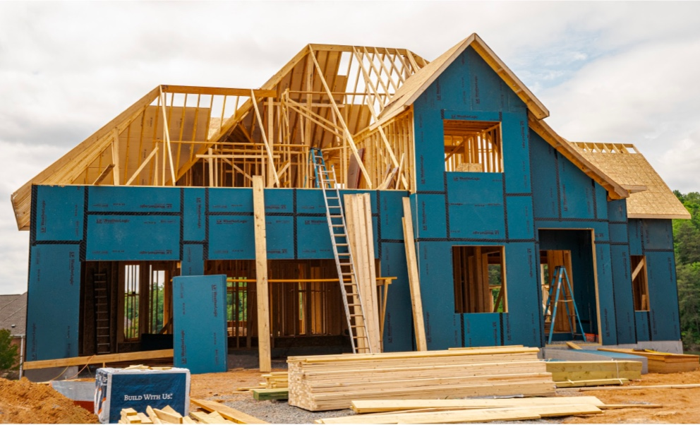 A large two story home under construction, with framing almost complete, and Weatherlogic panels being clad around the outside.