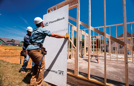 Worker adding flameblock sheet to a building frame.