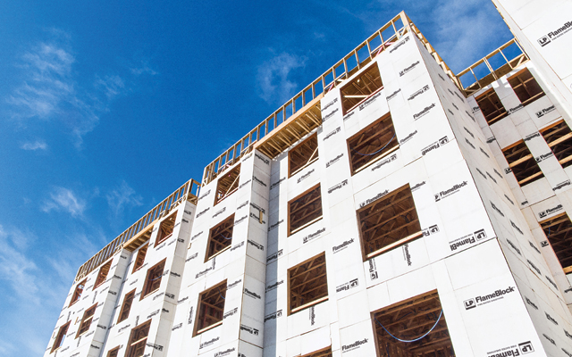 Looking up at a tall framed building covered in FlameBlock panels, under a clear blue sky.