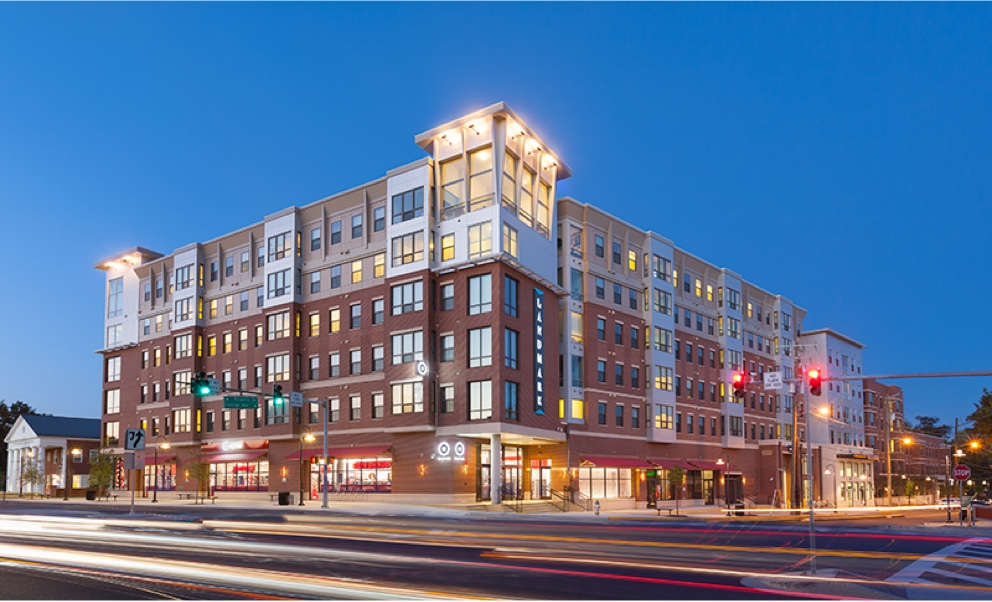 An exterior, lit up, dusk view of a finished commercial site, with apartments above and stores below.