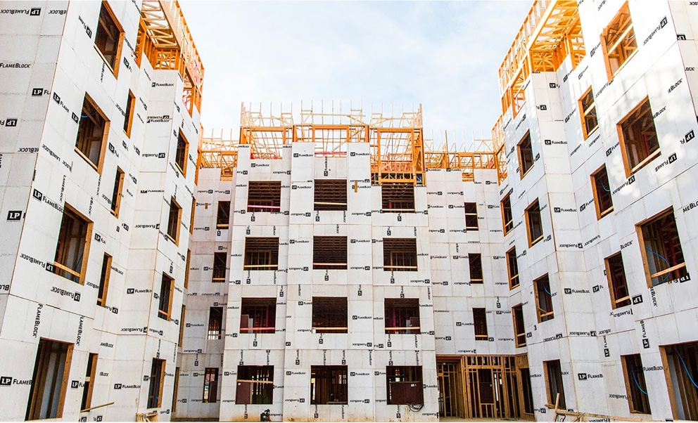 A view from the ground looking up at an in progress U-shaped four-story building with frames clad in Flameblock panels.