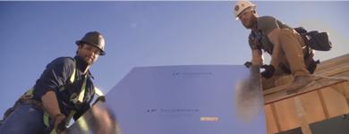 Deux ouvriers transportant une feuille de Techshield sur un toit sous un ciel dégagé.