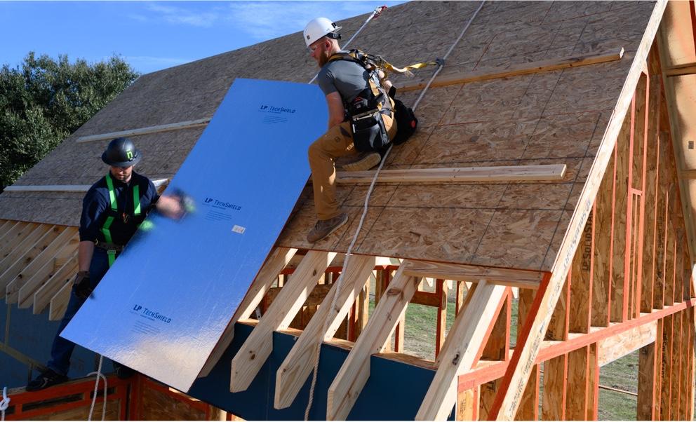Deux ouvriers plaçant une feuille de Techshield sur un toit en construction.