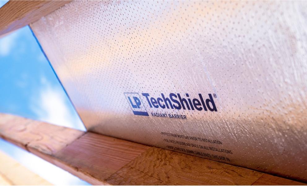 Vue de dessous d'un panneau de Techshield fixé à une poutrelle de toit avec un ciel ouvert en arrière-plan.