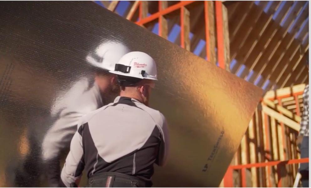 Un ouvrier portant une feuille réfléchissante de TechShield sur un chantier encadré.