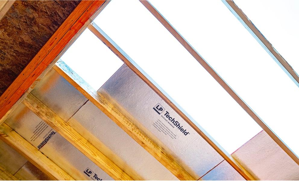 Vue à travers un toit à cadre, partiellement recouvert de panneaux Techshield réfléchissants, vers le ciel lumineux en arrière-plan.