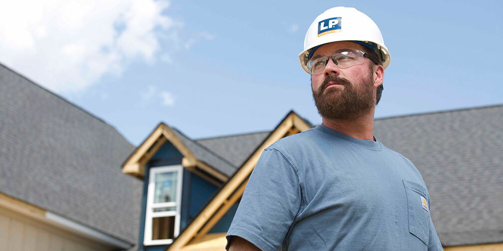 Man with LP hardhat with house in background